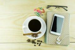 Telefone, café, vidros e livro de nota espertos no backgrou de madeira da tabela fotografia de stock royalty free