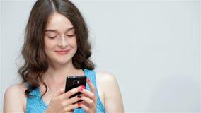 Telefone celular adolescente do uso da menina, fazendo os polegares acima video estoque