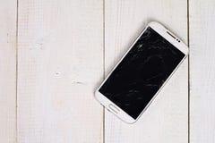 Telefone celular branco com a tela quebrada no fundo de madeira Fotos de Stock