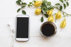 Telefone celular, café preto com a flora local do ylang amarelo do ylang da flor de Ásia imagens de stock royalty free