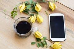 Telefone celular, café preto com a flora local do ylang amarelo do ylang da flor de Ásia imagem de stock