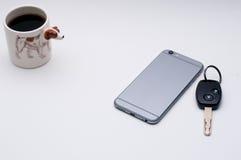 Telefone celular, chave do carro, xícara de café, lado do cão de Jack Russel do copo de café Fotos de Stock Royalty Free