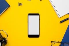 Telefone celular com bloco de notas branco, o caderno azul e a pena no fundo amarelo fotografia de stock