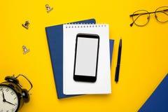 Telefone celular com bloco de notas branco, o caderno azul e a pena no fundo amarelo imagem de stock royalty free