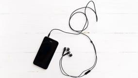 Telefone celular com fone de ouvido Imagem de Stock Royalty Free