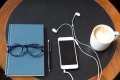 Telefone celular com fones de ouvido e vidros no encontro do caderno e da pena Imagem de Stock