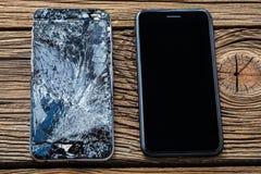 Telefone celular com o écran sensível quebrado no fundo de madeira fotos de stock royalty free