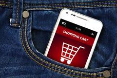 Telefone celular com o carrinho de compras no bolso das calças de brim Fotografia de Stock