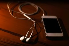 Telefone celular com os fones de ouvido no fundo de madeira imagens de stock royalty free