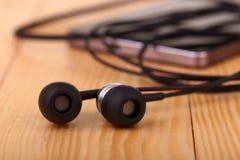 telefone celular com pares de fone de ouvido Fotografia de Stock Royalty Free