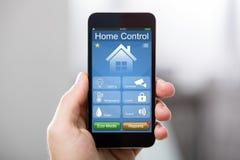 Telefone celular com sistema de controlo home em uma tela fotos de stock