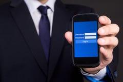 Telefone celular com a tela de início de uma sessão na mão do homem de negócio Fotografia de Stock