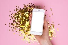 Telefone celular com a tela vazia branca na mão fêmea no fundo cor-de-rosa do papel da cor com confetes dourados fotografia de stock