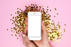 Telefone celular com a tela vazia branca na mão fêmea no fundo cor-de-rosa do papel da cor com confetes dourados fotos de stock