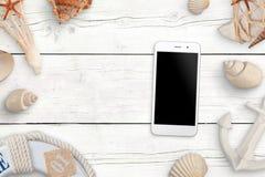 Telefone celular com a tela vazia para o modelo na tabela de madeira branca cercada com escudos imagens de stock
