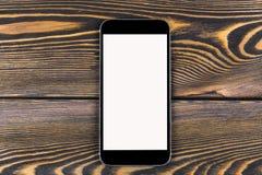 Telefone celular com zombaria da tela vazia isolado acima no fundo de madeira da tabela Smartphone na tabela de madeira Branco de Fotografia de Stock Royalty Free