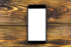 Telefone celular com zombaria da tela vazia isolado acima no fundo de madeira da tabela Smartphone na tabela de madeira Branco de Imagem de Stock