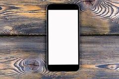 Telefone celular com zombaria da tela vazia isolado acima no fundo de madeira da tabela Smartphone na tabela de madeira Branco de Imagens de Stock