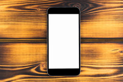 Telefone celular com zombaria da tela vazia isolado acima no fundo de madeira queimado da tabela Smartphone na tabela de madeira  Imagens de Stock