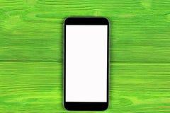 Telefone celular com zombaria da tela vazia isolado acima no fundo de madeira verde da tabela Smartphone na tabela de madeira Tel Imagens de Stock