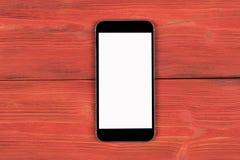 Telefone celular com zombaria da tela vazia isolado acima no fundo de madeira vermelho da tabela Smartphone na tabela de madeira  Imagens de Stock Royalty Free