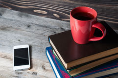 Telefone celular, copo de café e livros vazios no desktop de madeira Foto de Stock