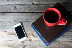 Telefone celular, copo de café e livros vazios no desktop de madeira Imagens de Stock