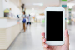 Telefone celular da posse da mão com hospital borrado Foto de Stock