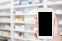 Telefone celular da posse da mão na farmácia Imagem de Stock Royalty Free
