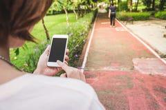 telefone celular da posse da mão no jardim Fotos de Stock