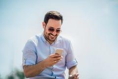 Telefone celular da terra arrendada do homem e cartão de crédito ocasionais novos de sorriso fotos de stock