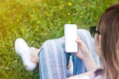 Telefone celular da terra arrendada da mulher com a tela vazia em sua mão Fundo da grama, raios do sol fotos de stock royalty free