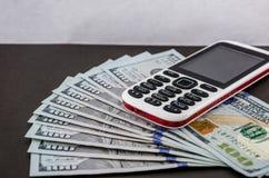 Telefone celular de botão de pressão em um fundo cinzento e em cem notas de dólar imagem de stock