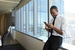 Telefone celular de Checking Messages On do homem de negócios foto de stock