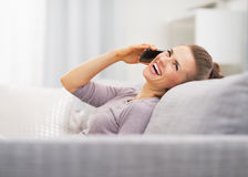 Telefone celular de fala da jovem mulher feliz ao sentar-se no sofá Imagem de Stock