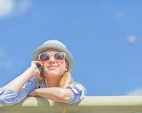 Telefone celular de fala da menina feliz do moderno na rua da cidade Fotografia de Stock Royalty Free