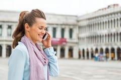 Telefone celular de fala da mulher no marco de san da praça Imagem de Stock
