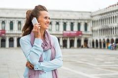 Telefone celular de fala da mulher no marco de san da praça Foto de Stock
