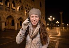 Telefone celular de fala de sorriso do turista da mulher na praça San Marco Imagens de Stock Royalty Free