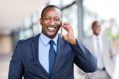 Telefone celular de fala do homem de negócios africano imagem de stock
