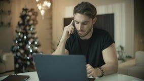 Telefone celular de fala do homem feliz no ano novo Homem de negócio que trabalha no Natal video estoque
