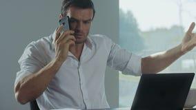 Telefone celular de fala do homem de negócio para o trabalho Freelancer irritado que faz o telefonema video estoque