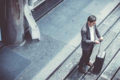 Telefone celular de fala do terno elegante asiático do desgaste do homem de negócios ao andar mantendo a mala de viagem exterior  fotografia de stock royalty free