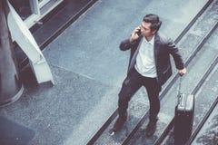 Telefone celular de fala do terno elegante asiático do desgaste do homem de negócios ao andar mantendo a mala de viagem exterior  fotos de stock