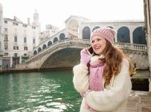 Telefone celular de fala do turista da mulher na frente da ponte de Rialto Fotos de Stock