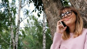 Telefone celular de fala e sorriso da moça emocional bonita Jovem mulher do moderno que usa o smartphone no parque video estoque