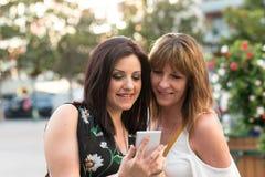 Telefone celular de observação feliz da mãe e da filha fora fotos de stock
