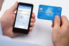 Telefone celular de Person With Credit Card And fotografia de stock