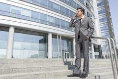 Telefone celular de resposta do homem de negócios completo do comprimento ao estar em etapas fora do escritório Imagens de Stock Royalty Free