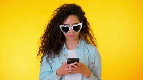 Telefone celular de sorriso e de utilização fêmea novo sobre o fundo amarelo Menina bonita da raça misturada que guarda e que tex imagem de stock royalty free